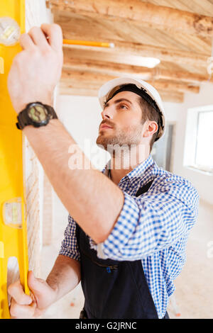 Close-up portrait of a construction builder holding yellow tape at the working area - Stock Photo