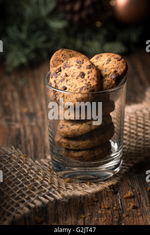 Fresh baked chocolate chip cookies in a glass on a rustic wooden table. - Stock Photo