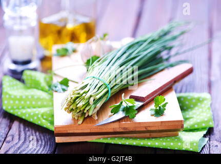 green onion on board and on a table - Stock Photo