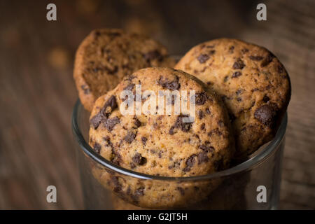 Close up of fresh baked chocolate chip cookies in a glass on a rustic wooden table. - Stock Photo