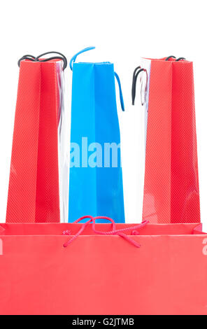 Shopping and gift bags in different colors as blue and red in closeup isolated on white background with text area - Stock Photo
