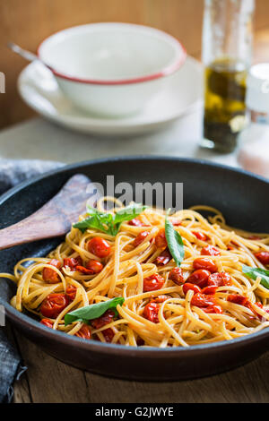 Freshly cooked  Fettuccine with cherry tomatoes in a sauce pan - Stock Photo