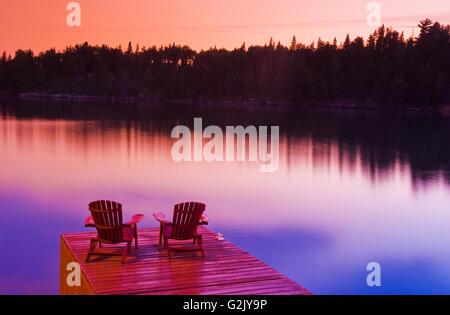 Muskoka chairs on dock, Lake of the Woods, Northwestern Ontario, Canada - Stock Photo
