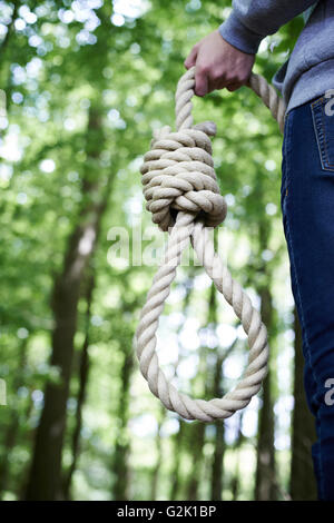 Depressed Man Contemplating Suicide By Hanging In Forest - Stock Photo