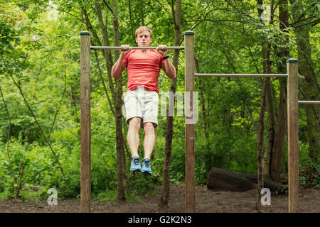 Male athlete doing muscle-up on horizontal bar - Stock Photo