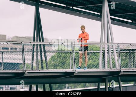Running man looking sportwatch. Male runner jogging using smart watch on metal bridge - Stock Photo