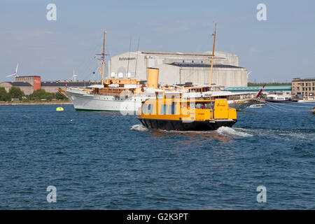 A yellow harbour bus passing the anchored Danish Royal Yacht HDMY Dannebrog at Holmen in the harbour of Copenhagen. - Stock Photo