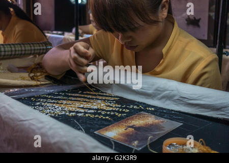 Diversity: Young female Asian girl person sewing silk in a weaving workshop, Hoi An, Vietnam - Stock Photo