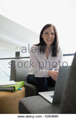 Portrait smiling adult education student using laptop - Stock Photo