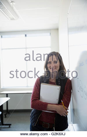 Portrait confident professor with notebook leaning on whiteboard in classroom - Stock Photo