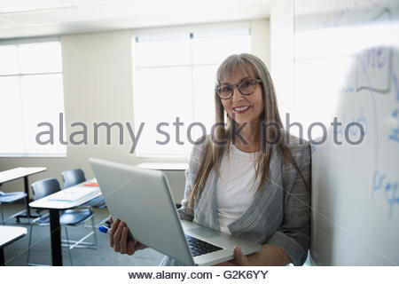 Portrait smiling professor with laptop at whiteboard in classroom - Stock Photo
