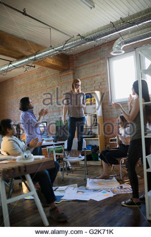 Coworkers clapping for designer standing on chair in office - Stock Photo