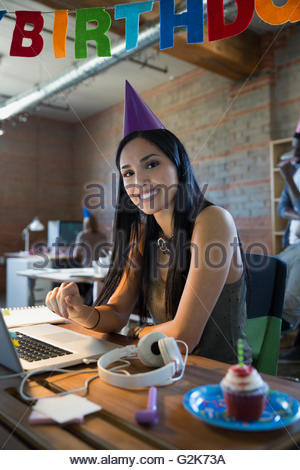 Portrait smiling businesswoman celebrating birthday at laptop - Stock Photo