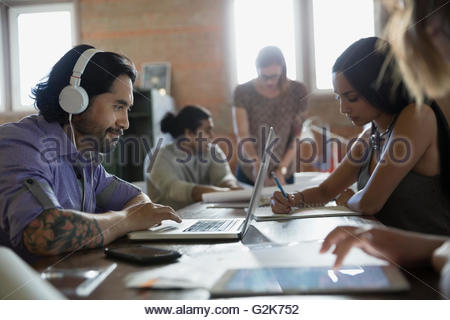Designers working at laptop and on proofs in office - Stock Photo