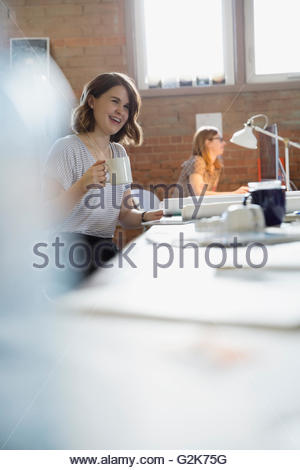 Smiling female designer drinking coffee in office - Stock Photo