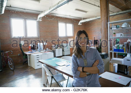 Portrait smiling designer with arms crossed in office - Stock Photo