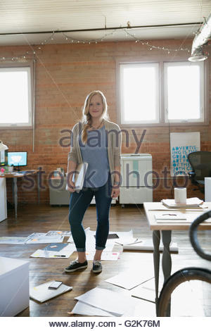 Portrait female designer holding laptop in office surrounded by paperwork - Stock Photo