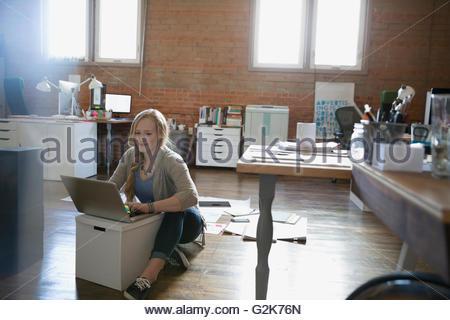 Female designer using laptop on floor in office - Stock Photo