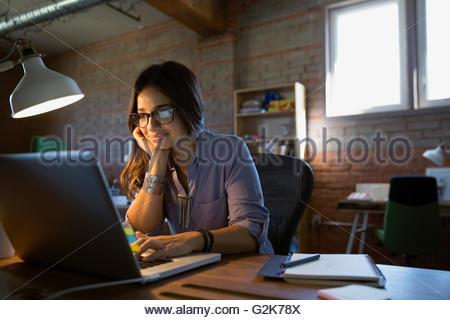 Female designer using laptop at desk in office - Stock Photo
