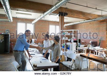 Designers handshaking over plans in office - Stock Photo