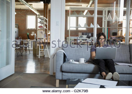 Female designer using laptop on sofa in office - Stock Photo