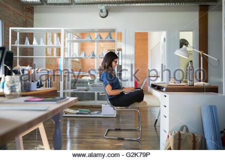 Creative businesswoman using laptop cross-legged in office - Stock Photo