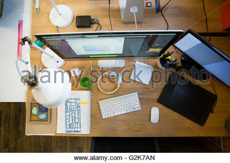 Overhead view of computers and digital tablet on desk - Stock Photo