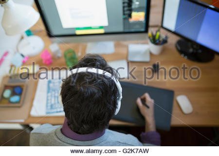 Designer with headphones using graphics tablet at computer - Stock Photo