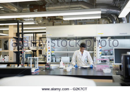 Scientist with clipboard working in laboratory - Stock Photo