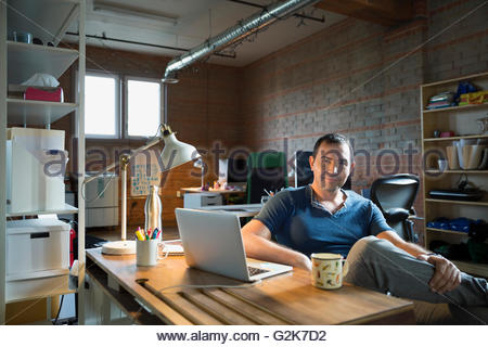 Portrait confident creative businessman at laptop in office - Stock Photo