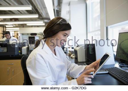 Scientist using digital tablet at desk in laboratory - Stock Photo