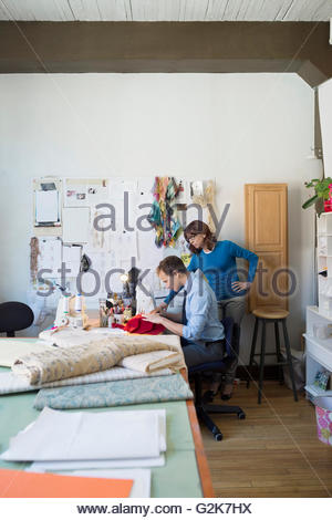 Dressmakers using sewing machine at workbench - Stock Photo