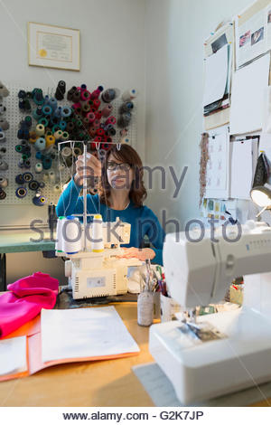 Dressmaker using sewing machine at workbench - Stock Photo