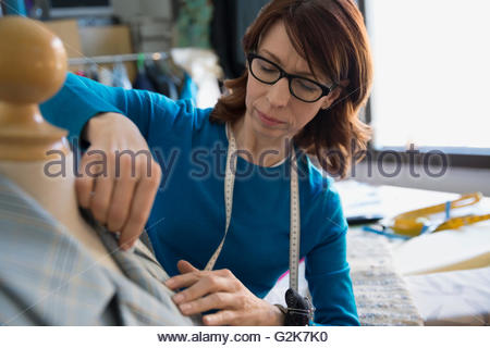 Dressmaker using tape measure on dressmakers model - Stock Photo