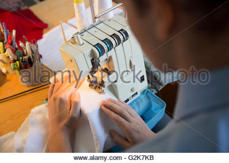 Dressmaker using sewing machine - Stock Photo