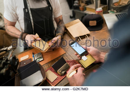 Customer using credit card reader in leather shop - Stock Photo