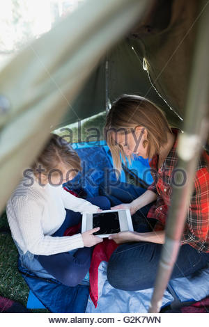 Mother and daughter playing game on digital tablet in tent - Stock Photo