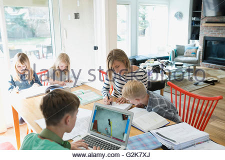 Mother helping son doing homework at dining table - Stock Photo