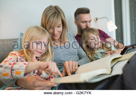 Family relaxing reading book and using digital tablet in bed - Stock Photo