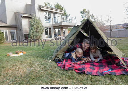 Father and daughters using digital tablet in backyard tent - Stock Photo