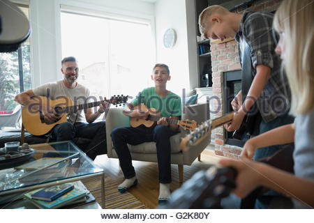Family playing guitars in living room - Stock Photo