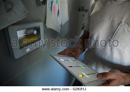 Man syncing home utilities with digital tablet - Stock Photo