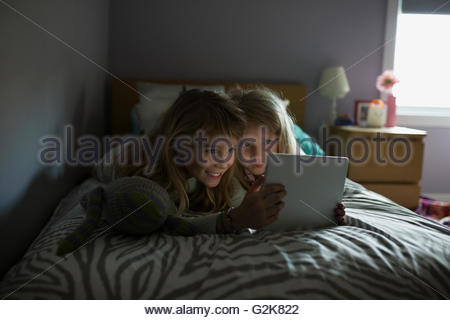 Sisters using digital tablet on bed - Stock Photo