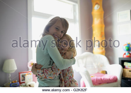 Portrait smiling sisters hugging in bedroom - Stock Photo