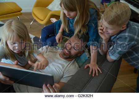 Father and children using digital tablet on sofa - Stock Photo