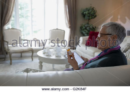 Senior woman with digital tablet checking prescription label - Stock Photo