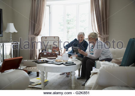 Senior women drinking tea and looking at old photographs - Stock Photo