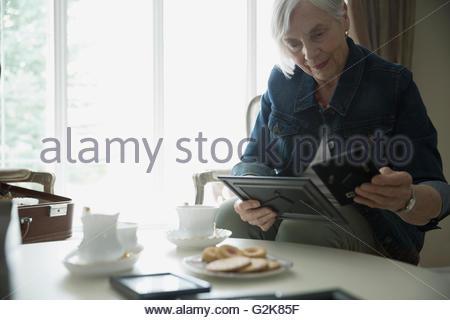 Senior woman drinking tea and looking at old photographs - Stock Photo