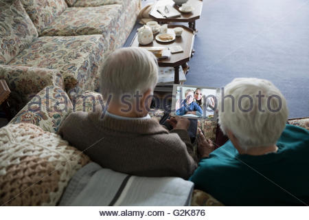 Senior couple video chatting with daughter and grandson on digital tablet - Stock Photo