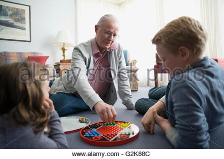 Grandfather and grandchildren playing Chinese checkers - Stock Photo